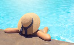 Woman with brown hat relaxing in swimming pool with blue water in sun , holiday concept royalty free stock photography