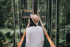 Woman in Brown Hat and White Sweater Walking in a Bridge Royalty Free Stock Photography
