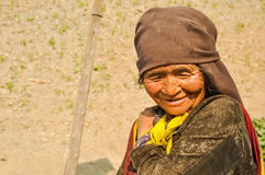Woman with brown headcloth in Nepal. Dolpo, Nepal - circa May 2012: Old native woman with wrinkled face and brown headcloth looks down and smiles nicely in Dolpo Stock Photos