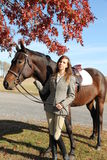 Woman with Brown Horse in Fall. Equestrian with bay warmblood standing under Fall Tree Royalty Free Stock Image
