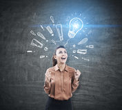 Woman in brown, light bulb and exclamation marks Stock Photo
