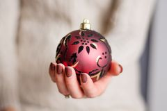 Woman with brown manicure nails polish holding red Christmas ball. Beautiful girl with brown manicure nails polish holding red Christmas ball decoration royalty free stock photography