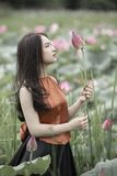 Woman in Brown Shirt Holding Pink Petaled Flower royalty free stock photography