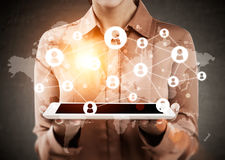 Woman in brown shirt is holding tablet with world map and network sketches. Close up of woman holding tablet. Network sketches and world map are seen on the stock photo
