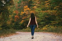 Woman in Brown Sleeveless Dress and Blue Jeans Standing on Gray Path Road stock photos