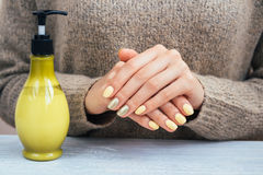 Woman in a brown sweater showing hands with yellow manicure, clo Stock Photography