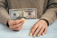 Woman in brown sweater with yellow manicure holding a banknote o Stock Photo