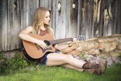 Woman in Brown Tank Top With Acoustic Guitar Sitting on Green Grass Beside Brown Wooden Fence Royalty Free Stock Photos