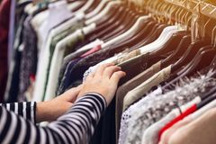 Woman browsing through clothing at second hand street market royalty free stock photo