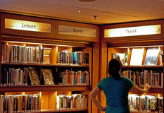 Woman Browsing Cruise Ship Library. A woman browses the cruise ship library for books Royalty Free Stock Photography