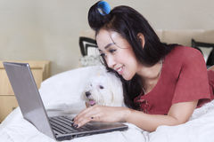 Woman browsing internet with dog on bed Stock Photo