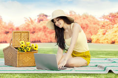 Woman browsing internet with laptop at park Royalty Free Stock Photos