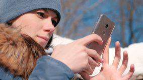 Woman is browsing internet pages on mobile phone sitting in winter park. Closeup face.  stock video footage