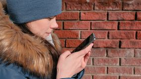 Woman is browsing internet pages on mobile phone sitting in winter park. Closeup face side view. Woman is browsing internet pages on mobile phone sitting in stock video