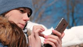 Woman is browsing internet pages on mobile phone sitting in winter park. Closeup face. Woman is browsing internet pages on mobile phone sitting in winter park stock footage