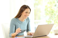 Woman browsing on line content in a laptop. Woman holding eyeglasses browsing on line content in a laptop on a desk at home Stock Photos