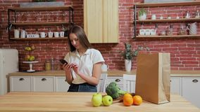 Woman browsing on mobile phone at home kitchen. Young woman browsing on smartphone smiling happy. Woman browsing on mobile phone at home kitchen. Young woman stock video