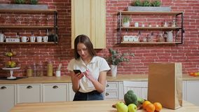 Woman browsing on mobile phone at home kitchen. Young woman browsing on smartphone smiling happy. Woman browsing on mobile phone at home kitchen. Young woman stock footage