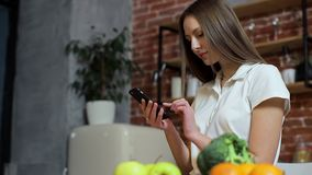 Woman browsing on mobile phone at home kitchen. Young woman browsing on smartphone smiling happy. Woman browsing on mobile phone at home kitchen. Young woman stock video footage