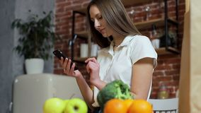 Woman browsing on mobile phone at home kitchen. Young woman browsing on smartphone smiling happy. stock video footage