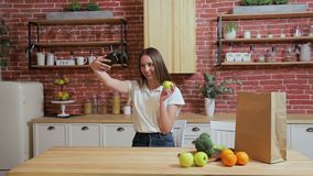 Woman browsing on mobile phone at home kitchen. Young woman browsing on smartphone smiling happy. A woman eats an apple stock footage