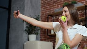Woman browsing on mobile phone at home kitchen. Young woman browsing on smartphone smiling happy. A woman eats an apple. And make photo stock video footage