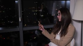 Woman browsing phone sitting near the window with panoramic city view at night. Tired young woman is browsing smartphone sitting near the window with panoramic stock video footage