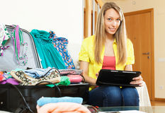 Woman browsing places to visit with tablet before leave. Smiling young woman browsing places to visit with tablet before going on leave stock photo