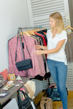 Woman browsing through rail clothes Stock Images