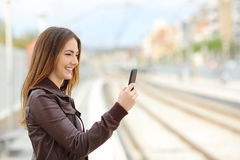 Woman browsing social media in a train station. Happy woman browsing social media in a train station with the railways in the background Royalty Free Stock Images