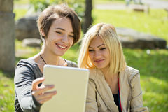 Woman browsing tablet in the park Royalty Free Stock Photography