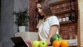 Woman browsing on tablet PC at home kitchen. Young woman browsing on Tablet PC and smiling happy. stock footage