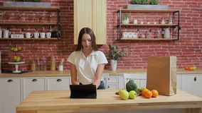 Woman browsing on tablet PC at home kitchen. Young woman browsing on Tablet PC and smiling happy. stock video