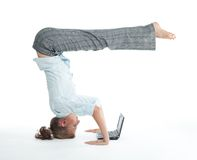 Woman browsing in unusual pose. Attractive woman browsing on laptop in unusual yoga pose heels over head stock photography