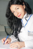 Woman brunette doctor writing medical history Stock Photos