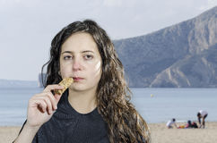 Woman brunette eating a energy bar in a beach. Royalty Free Stock Photography