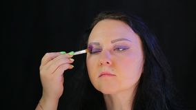 Woman brunette with eye makeup purple shadow. The average plan stock video