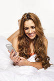Woman laughing as she reads a text message Royalty Free Stock Photography