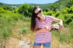 Woman brunette in sunglasses and striped t-shirt keeping turtle in her hands in the forest. royalty free stock photo