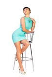 Woman brunette in turquoise dress sits on chair Royalty Free Stock Image