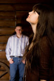 Woman brunette and young man in wooden log hut. Beautiful young woman brunette and young man in wooden log hut, woman standing near wall on background, focus on Royalty Free Stock Photography