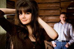 Woman brunette and young man in wooden log hut. Beautiful young woman brunette and young man in wooden log hut, woman standing near wall on background, focus on Stock Images
