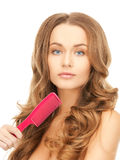 Woman with brush. Beautiful woman with long curly hair and brush Royalty Free Stock Image