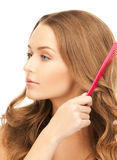Woman with brush. Beautiful woman with long curly hair and brush Royalty Free Stock Photos