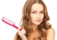 Woman with brush. Beautiful woman with long curly hair and brush Stock Photo