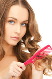Woman with brush. Beautiful woman with long curly hair and brush Royalty Free Stock Photography