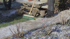 Woman with brush cleaning path. In winter day stock footage
