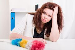 Woman with brush does not have strength to clean up dust Stock Foto