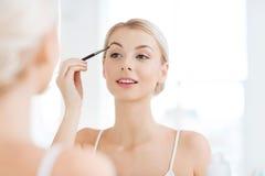 Woman with brush doing eyebrow makeup at bathroom Royalty Free Stock Photo