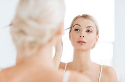 Woman with brush doing eyebrow makeup at bathroom Royalty Free Stock Images